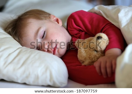 Healthy child, sweetest blonde toddler girl sleeping in bed holding her teddy bear - stock photo