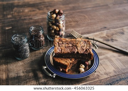Healthy coffee chocolate cake with hazelnut, chia seeds and flax seeds on wooden background - stock photo