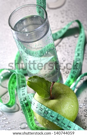 Healthy concept - apple glass of water and tape - stock photo