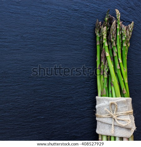 Healthy concept. Bunch of organic fresh asparagus on a grunge stone table. Selective focus, copy space background, flat lay - stock photo