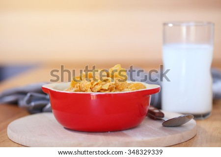 healthy continental breakfast consists of cup of milk, bowl of cereals.