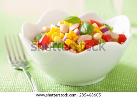 healthy corn salad with tomato onion white bean basil - stock photo