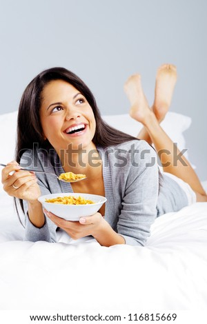 healthy cornflakes breakfast in bed woman eating and happy - stock photo