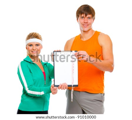 Healthy couple in sportswear showing clipboard with measuring tape isolated on white - stock photo