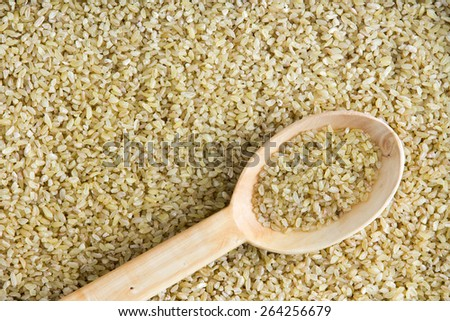 Healthy cracked wheat background texture with a diagonally placed wooden spoon and copy space for a cooking concept - stock photo