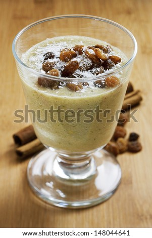 Healthy creamy smoothie with dried raisins and shredded coconut decoration on wooden table. Studio shot on daylight, shallow depth of field.