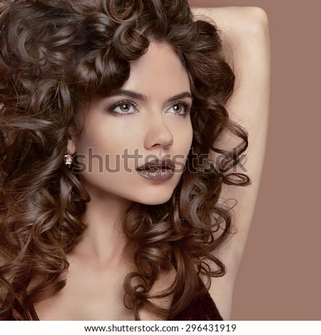 Healthy curly hair. Beauty Makeup. Brunette girl model with fashion lips, wavy hairstyle. Beautiful woman isolated on beige studio background.