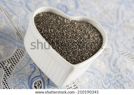 Healthy dark chia seeds in heart container - stock photo