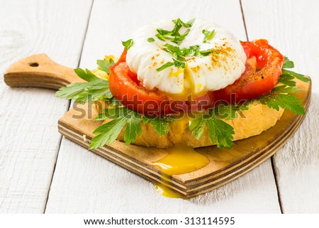 Healthy, delicious breakfast: poached egg on toast with tomatoes and parsley in a small wooden board on a white background - stock photo
