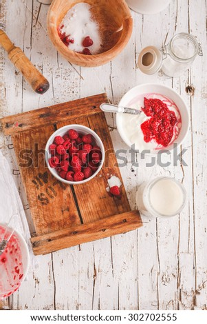 Healthy dessert for breakfast with greek yogurt and ripe raspberries from above on vintage chalkboard with pestle and mortar. Rustic style. see series - stock photo