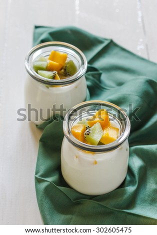 Healthy dessert: homemade yogurt with mango and kiwi served in small glass of bottle put on green cloth and white wood background. - stock photo