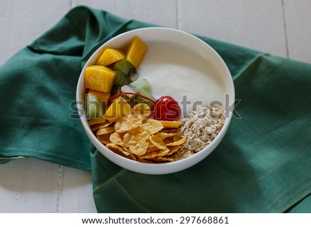 Healthy dessert: homemade yogurt with mango cornflake oat cherry and kiwi served in white cup  put on green cloth and white wood background. - stock photo