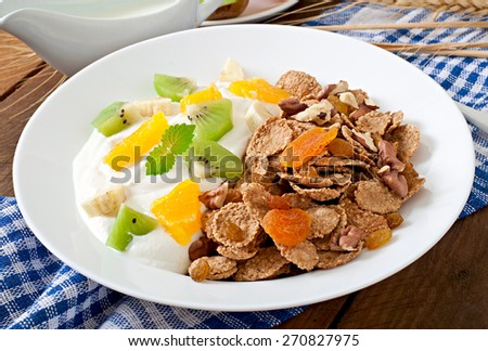 Healthy dessert with muesli and fruit in a white plate on the table - stock photo