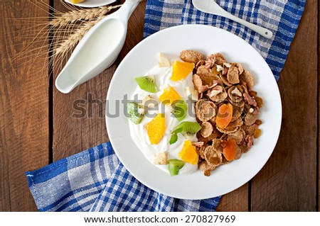 Healthy dessert with muesli and fruit in a white plate on the table. Top view. - stock photo