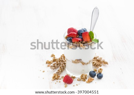 healthy dessert with natural yogurt, muesli and berries in a glass on white background, horizontal - stock photo