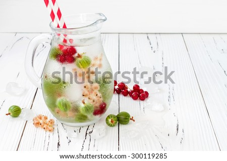 Healthy detox berry infused flavored water. Summer refreshing homemade drink with gooseberries and white and red currant on white wooden table. Copy space background - stock photo