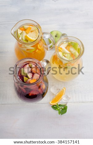 Healthy detox fruit infused flavored water. Summer refreshing homemade cocktail with fruits on white wooden table top view - stock photo