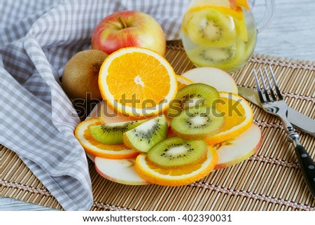 Healthy detox fruit infused flavored water. Summer refreshing homemade cocktail with fruits on white wooden table - stock photo