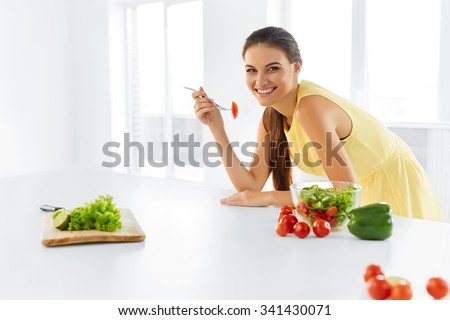 Healthy Diet. Beautiful Smiling Woman Eating Fresh Organic Vegetarian Salad In Modern Kitchen. Healthy Eating, Food And Lifestyle Concept. Health, Beauty, Dieting Concept. - stock photo