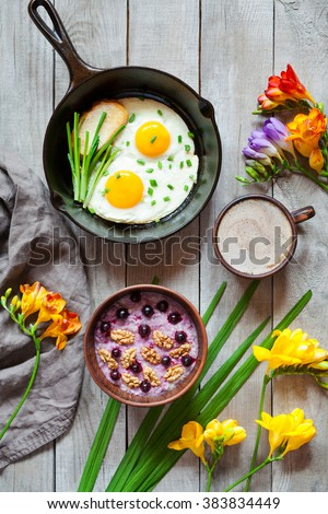 Healthy diet breakfast with spring morning mood, oatmeal porridge with nuts and blackberry, coffee and fried eggs in cast iron skillet on vintage wooden background. Top view - stock photo