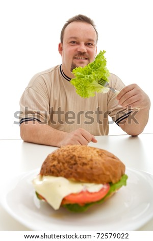 Healthy diet choices concept with overweight man eating lettuce instead of burger - stock photo