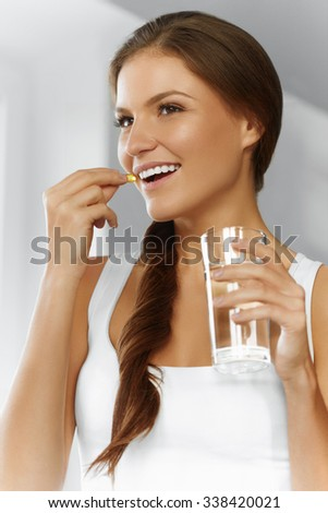 Healthy Diet, Eating, Lifestyle. Happy Smiling Woman Taking Pill With Cod Liver Oil Omega-3 And Holding A Glass Of Fresh Water. Healthcare And Beauty. Vitamin D, E, A Fish Oil Capsules. Nutrition.  - stock photo