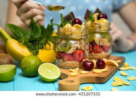 healthy diet. girl hand with a spoon and oatmeal with berries and fruits - stock photo