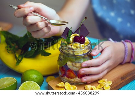 healthy diet. girl hand with a spoon and oatmeal with berries and fruits, measurer. foodphoto  - stock photo