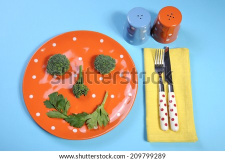 Healthy diet health food concept with happy smiley face made from broccoli and celery on a fun orange polka dot plate with salt and pepper shakers, and colorful cutlery on a pale blue background. - stock photo