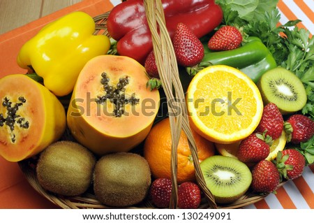 Healthy diet - sources of Vitamin C - oranges, strawberry, bell pepper capsicum, kiwi fruit, paw paw, spinach dark leafy greens and parsley. - stock photo