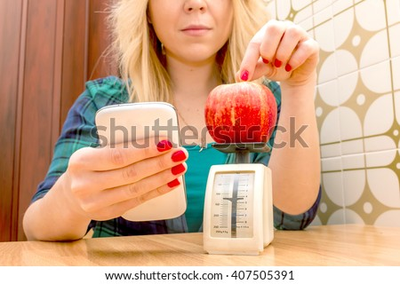 healthy diet weight loss app on smartphone- young woman on a diet plan, weighing an apple to calculate calories intake using a smartphone app - concept of how modern technology can help healthy life - stock photo