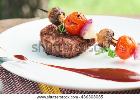 Healthy dinner of steak and vegetable skewers served on a white plate