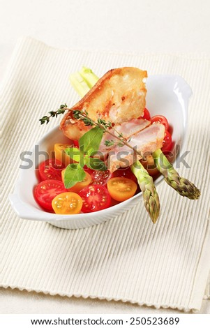 Healthy dish of cherry tomatoes, asparagus spears and slices of meat - stock photo