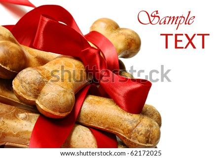 Healthy dog treats with red satin ribbon on white background with copy space.  Macro with shallow dof. - stock photo