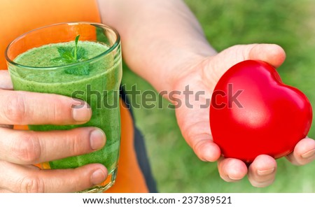 Healthy drink - green smoothie in hand - stock photo