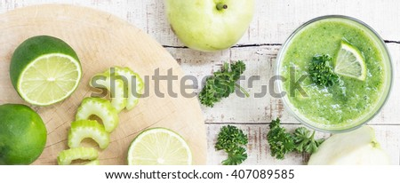 Healthy drink ingredients on white wooden table. Celery stalk, lime, green apple, guava with knife on cutting board. Vegan, diet, vegetarian food, detox. - stock photo