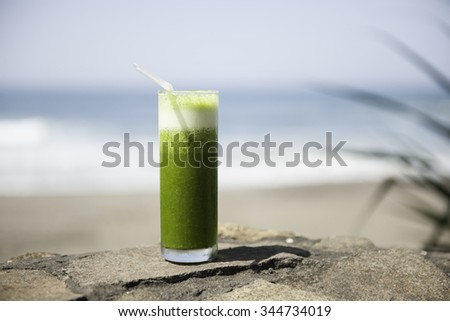 Healthy drink on the beach, ocean in the background - stock photo