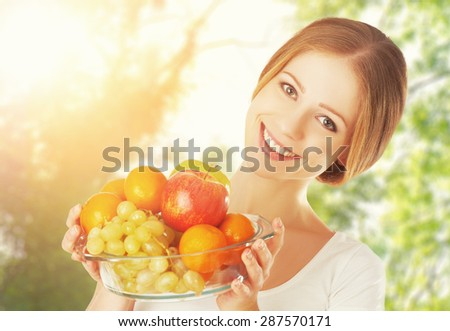 Healthy Eating. a woman with a plate of fruit in the summer on the nature - stock photo
