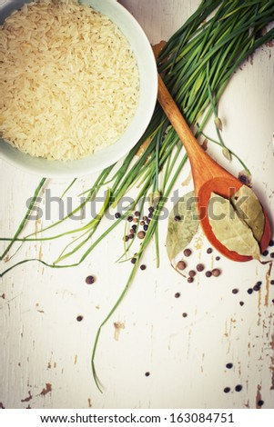 Healthy eating background with bowls of rice and spices,fresh herbs,with green spring onions, bay leafs - stock photo