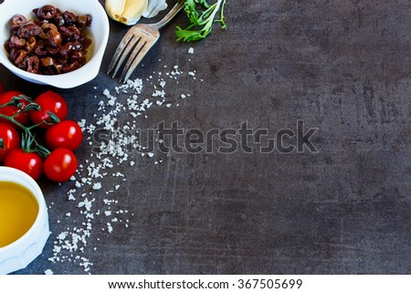 Healthy eating background with salad preparation ingredients (olive oil, herbs leaves, tomatoes, garlic and olives) on dark vintage table with space for text. - stock photo