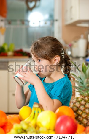 Healthy eating - Child drinking milk, lots of fresh fruit on the table in front - stock photo