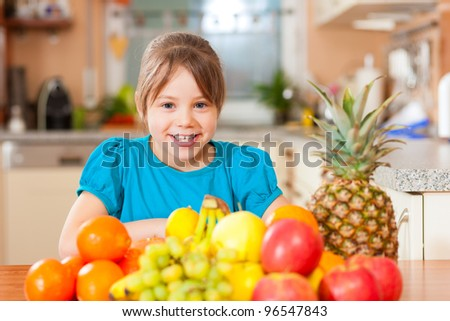 Healthy eating - child sitting in the kitchen with different kinds of fruits for breakfast food - stock photo