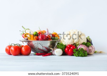 Healthy eating. Clean fresh vegetables in metal colander on a wooden table. - stock photo