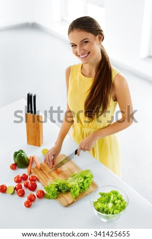 Healthy Eating. Close Up Beautiful Smiling Woman Cooking Fresh Organic Food And Making Vegetable Salad In Kitchen. Diet And Lifestyle Concept. Vegetarian Food Preparation. Nutrition. - stock photo