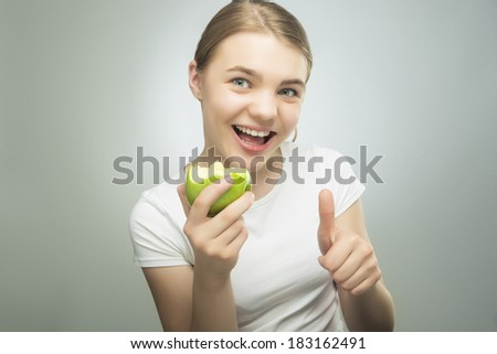 Healthy Eating Concept: Caucasian Teenage Girl Eating Green Apple with Smile on Her Face. Showing Thumbs Up sign. Horizontal Image - stock photo