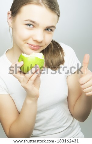 Healthy Eating Concept: Caucasian Teenage Girl Holding Green Apple and Smiling. Showing Thumbs Up sign. Vertical Image - stock photo