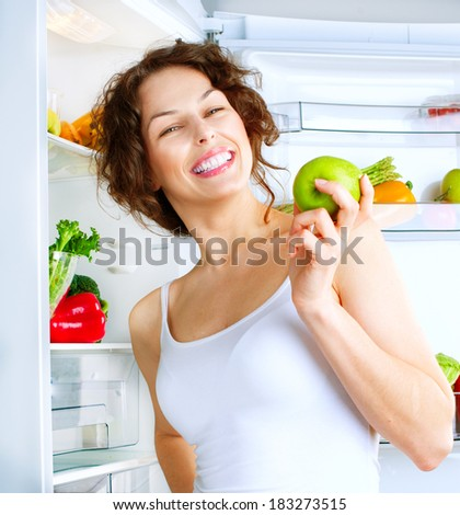 Healthy Eating Concept .Diet. Beautiful Young Woman near the Fridge  with healthy food. Fruits and Vegetables in the Refrigerator