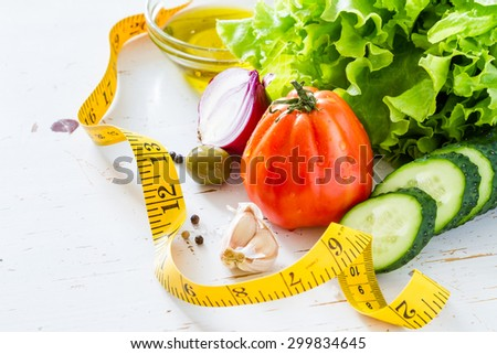 Healthy eating concept - fresh vegetables and measuring tape, white wood background