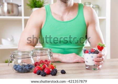 Healthy eating concept. Man with delicious yogurt with fresh berries - stock photo