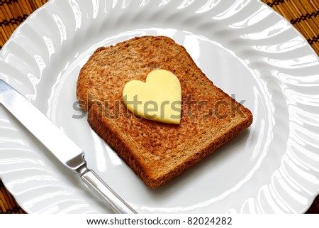 Healthy eating concept - piece of whole wheat toast on a white plate with a heart shaped symbol of butter - stock photo